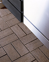 Brick flooring laid in an alternate grid fashion contrasts with the stainless steel units in this contemporary kitchen