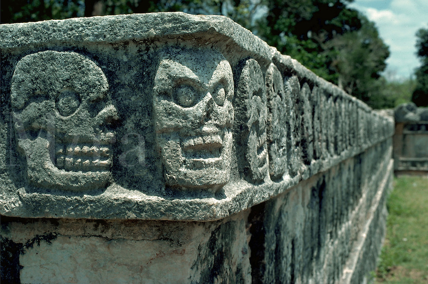 A wall of carved stone skulls called Tzompantli at the Mayan ruins of Chichen Itza. Yucatan, Mexico.