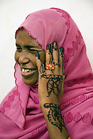 "Djibouti. Djibouti province. Djibouti. ""Oui à la vie"" (Yes to life) was the first djiboutian association for seropositive people living with the HIV Aids disease. Seropositive smiling muslim woman displays newly applied Henna on her hand.Temporary tattoos. Hijab on her head, Gold tooth. The Global Fund through the djiboutian Ministry of Health supports the programm with an Aids grant (financial aid).  © 2006 Didier Ruef"