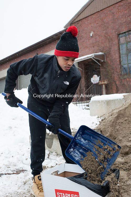 WATERBURY, CT-26 January 2015-012615EC06-   Waterbury resident Deante Petteway fills a container with free sand offered by the Department of Public Works on East Aurora Street Monday. Erin Covey Republican-American