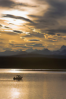 Sport fishermen troll for lake trout on a summer evening. Summit Lake and the Alaska Range in the distance, Interior, Alaska.
