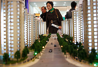 Visitors look at models of apartments at a real-estate fair in Shanghai, China. The Chinese government is likely to cut the business and income tax levied on property transactions to further stimulate the real estate market, the English China Daily reported on Friday, recent data has shown that China's economy has slowed down more drastically than previously expected..12 Dec 2008