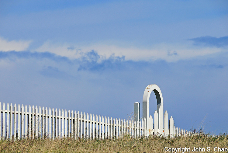 White picket fence and gate set against a blue sky with clouds. American Camp, San Juan Island National Historical Park, San Juan Islands, Washington State,
