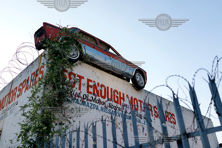 A half of a car mounted on a wall serves as an advertisement for a motor spares business in downtown Johannesburg. After a steep decline in the 1990s, the inner city is now a peculiar mix of interspersed working class neighbourhoods, down-and-out and gentrified real estate, all within a few minutes walk of each other.
