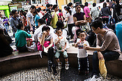 Tourists sit and relax at the fountain area in Central Macau, China.