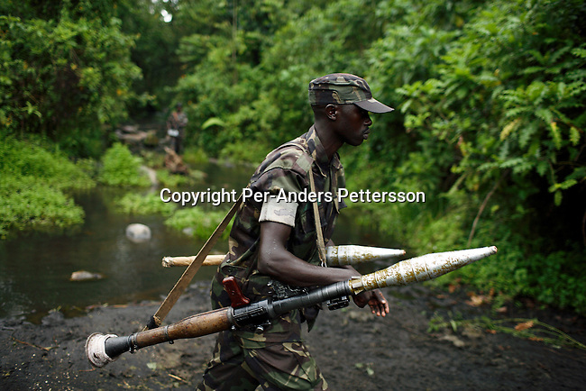KILOLIRWE, DRC OCTOBER 2: A soldiers loyal to the elusive rebel leader General Laurent Nkunda walk armed across a small river after a training exercise on October 2, 2006 in Kilolirwe, outside Goma, DRC. General Nkunda has been charged with was crimes and he is one of the few rebel leaders that has not joined the current peace deal and elections in Congo, DRC. He has about 2-4000 soldiers in his army. Nkunda is accused of numerous war crimes and other serious human rights violations the past few years including summary executions, torture, and rape committed under his command. The incidents are a mainly in Bukavu in 2004 and in Kisangani in 2002. Nkunda is a Congolese Tutsi, and he was born in Congo?s North Kivu Province, close to Rwanda. .(Photo by Per-Anders Pettersson/Getty Images).