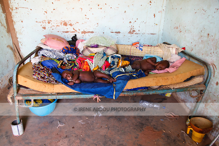 Two Fulani baby girls sleep on a bed in the town of Djibo in northern Burkina Faso.  Because of the early age of marriage for girls, it is common to see children of two generations in the same age group.  In this photo, the baby on the right is the aunt of the baby on the left.