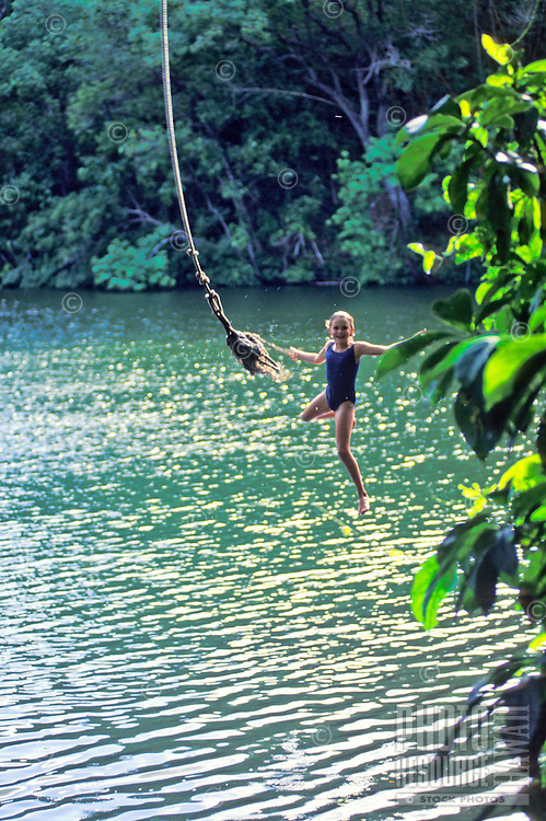 Young girl jumping off rope swing at Green lake, Big Island of Hawaii
