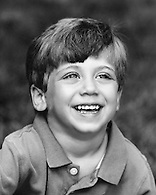 Black & white portrait of smiling young boy.