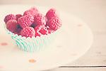 fresh, ripe, raspberries in a cupcake liner