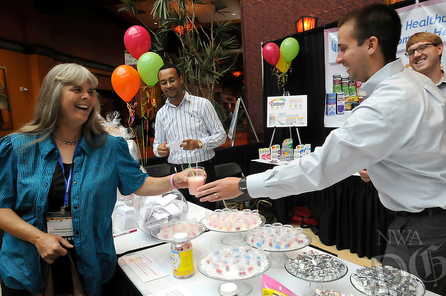 Note: Tripp is correct.<br /> STAFF PHOTO FLIP PUTTHOFF <br /> CONFERENCE SAMPLES<br /> Melinda McGarrah, left, samples a vitamin drink on Tuesday Sept. 16 2014 served by Tripp Cashion at the Northwest Arkansas Business Women's Conference in Rogers.