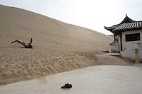 A lone pair of shoes in front of huge sand dunes at the tourist attraction Ming Sha Shan. Desertification is the process by which fertile land becomes desert, typically as a result of drought, deforestation, or inappropriate agriculture. Dunhuang, Gansu Province. China