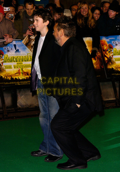 "FREDDIE HIGHMORE & LUC BESSON.""Arthur And The Invisibles"" UK film premiere at Vue Leicester Square, London, UK..January 25th, 2007.full length crouching profile black suit jacket jeans denim.CAP/CAN.©Can Nguyen/Capital Pictures"
