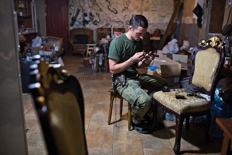 UKRAINE, Pisky: Vladimir is cleaning his weapon at night inside the kitchen of the house.<br />