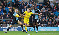 Chris Maguire of Oxford United battles with Luke O'Nien of Wycombe Wanderers and Anthony Stewart of Wycombe Wanderers during the Sky Bet League 2 match between Wycombe Wanderers and Oxford United at Adams Park, High Wycombe, England on 19 December 2015. Photo by Andy Rowland.