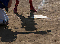 A girls softball league catcher and batter's shadow are cast across home plate as the ball  is caught.<br />