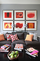 Orange and red scatter cushions and artwork inject a burst of colour into this grey living room