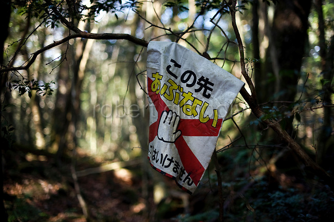 A sign warning people of danger ahead is attached to a branch of a tree in Aokigahara Jukai, better known as the Mt. Fuji suicide forest, which is located at the base of Japan's famed mountain west of Tokyo, Japan.