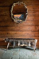 A frame of antlers hangs above a bench covered with an animal skin in the entrance hall