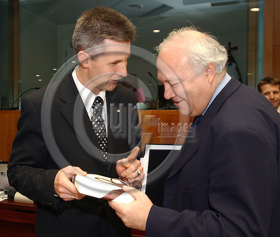 Brussels-Belgium - November 02, 2004---European Ministers of Foreign Affairs meet on General Affairs and External Relations, at the 'Justus Lipsius', seat of the Council of the European Union in Brussels; here, Artis PABRIKS (le), Foreign Minister of Latvia, handing over a present (Latvian chocolate) to Miguel Angel MORATINOS (ri), Minister for Foreign Affairs and Cooperation of Spain, at the beginning of the meeting ---Photo: Horst Wagner/eup-images