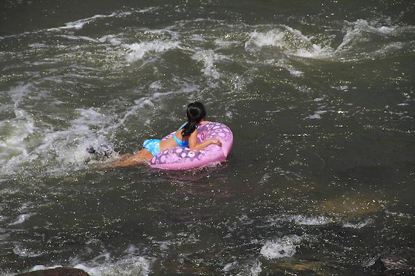 Girl in inner tube in Confluence Park, Denver, Colorado, USA.