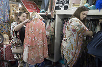NWA Democrat-Gazette/CHARLIE KAIJO Brandie Samples of Electic Ruby Red clothing booth (left) sets up a mannequin as Amanda Cooper of Fayetteville (right) tries on a garment during the Vintage Market Days event, Saturday, April 13, 2019 at the Benton County Fairgrounds in Bentonville.