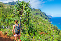 A hiker on the Kalalau Trail looks out over the Napali (or Na Pali) coastline, Kaua'i.