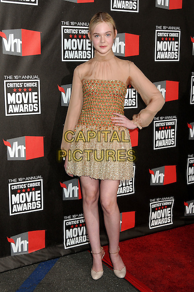 ELLE FANNING .16th Annual Critics' Choice Movie Awards held at the Hollywood Palladium, Hollywood, California, USA, 14th January 2011..full length sheer beige long sleeve see thru through gold dress hand on hip red sequined sequin  shoes cream high polo neck  beaded .CAP/ADM/BP.©Byron Purvis/AdMedia/Capital Pictures.