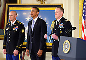 United States President Barack Obama listens to the citation prior to awarding awarding the Medal of Honor for conspicuous gallantry to Staff Sergeant Ty M. Carter, U.S. Army, during a ceremony in the East Room of the White House in Washington, D.C. on Monday, August 26, 2013.  Staff Sergeant Carter is being honored for courageous actions while serving as a cavalry scout with Bravo Troop, 3rd Squadron, 61st Cavalry Regiment, 4th Brigade Combat Team, 4th Infantry Division, during combat operations in Kamdesh District, Nuristan Province, Afghanistan on October 3, 2009. Staff Sergeant Carter is the fifth living veteran to be awarded the Medal of Honor for actions in Iraq or Afghanistan.  <br /> Credit: Ron Sachs / CNP