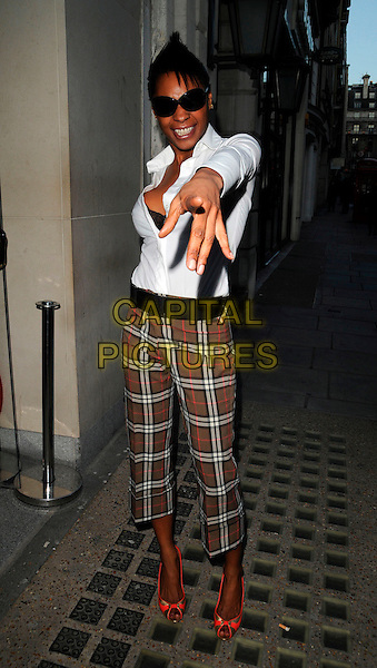 SONIQUE .The End Of Summer Ball in Berkeley Square launch party, Nobu restaurant, London, England..April 7th, 2008.full length white shirt brown plaid tartan orange gold shoes sunglasses shades arm hand pointing cropped.CAP/CAN.©Can Nguyen/Capital Pictures.