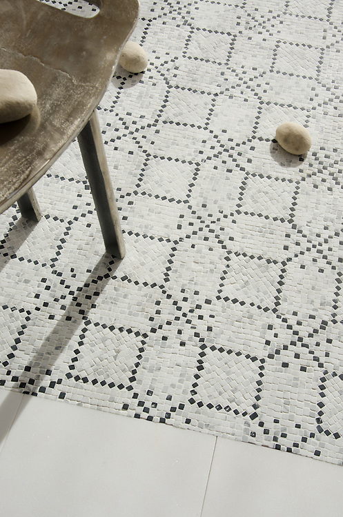 Augustine, a hand-cut stone mosaic, shown in hand-chopped tumbled Calacatta Tia and Nero Marquina, is designed by Paul Schatz as part of the Legend™ collection by New Ravenna.
