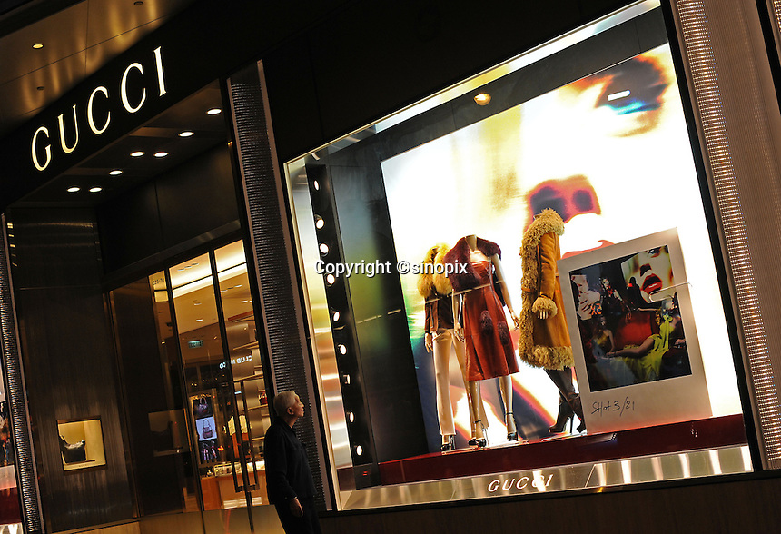 An old man passes an advert for Gucci in Hong Kong. Gucci is leading centre for luxury fashion brands carry the complete range of one of the world's top fashion brands products................