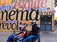 France. Department Ile-de-France. Paris. MK2 Quai de seine on the Bassin de la Villette. Two men ride a blue Yamaha motorbike and pass in front of a wall with written painted words: Egality, Desire, Sex, Revolt,..  20.05.2011 © 2011 Didier Ruef