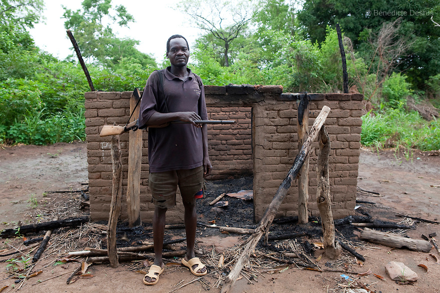 23 may 2010 - Western Equatoria State, South Sudan - Santo Samuel Ufi stands in front of his house. The Lord's Resistance Army (LRA) stole his possesions and burnt his house in Zangia, Western Equatoria State on may 17, 2010. He carries a localy made gun for self-defense since the attacks. The LRA has attacked a number of roads, villages, and clinics near the town of Tambora over the last week pushing thousands of people to flee to Tambora for protection. Western Equatoria state has been rocked by LRA activities since 2006. Thousands of people have been forced from their homes as brutal attacks continue against the civilian population in the region and neighboring DRC and CAR. Photo credit: Benedicte Desrus