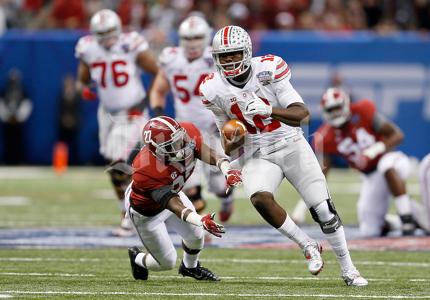 Ohio State Buckeyes quarterback Cardale Jones (12) runs for a big gain past Alabama Crimson Tide defensive back Nick Perry (27) during the second quarter in the Allstate Sugar Bowl college football playoff semifinal at Mercedes-Benz Superdome in New Orleans on Thursday, January 1, 2015. (Columbus Dispatch photo by Jonathan Quilter)