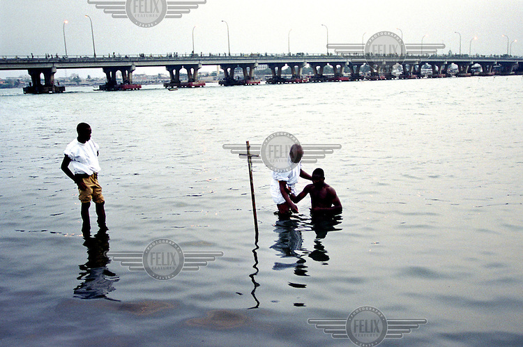 ©Sven Torfinn/Panos Pictures..Benin, Cotonou, 2002.boy is baptised in the river by a priest with a cross, in the background a bridge..members the 'eglise celeste' (celestial church), where they practise an kind of Christianity that has adopted African elements, tradition, culture, they for instance tolerate polygamy..sect, religion, belief..
