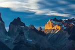 Sunset light illuminates the yellow granite face of Monte Almirante Nieto.    At left is the East Horn or Cuerno of the Curenos del Paine, with Monte Almirante Nieto on the right.  Between the Cuernos and Monte Almirante Nieto are the tips of Torre Sur and Torre Central.  Torres del Paine National Park in Patagonia, Chile.  A UNESCO World Biosphere Reserve.  A polarizing filter was used to cut haze, increasing the contrast.