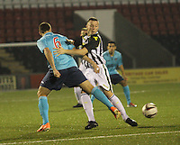 Declan Hughes gets a foot in to tackle Stephen Husband in the St Mirren v Dunfermline Athletic Scottish Professional Football League Under 20 match played at the Excelsior Stadium, Airdrie on 11.12.13.