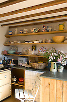 In this country kitchen plates and dishes are arranged with pleasing simplicity on open shelves against whitewashed walls