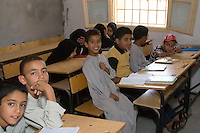 Surman, Libya.  Boys and Girls in Classroom at the Madrasa of Sidi Rashid al-Galili, where they study to memorize the Koran.  Young girls wear the traditional Libyan head scarf.  Boys may wear traditional garments, but western or European sport shirts or T-shirts are more popular.