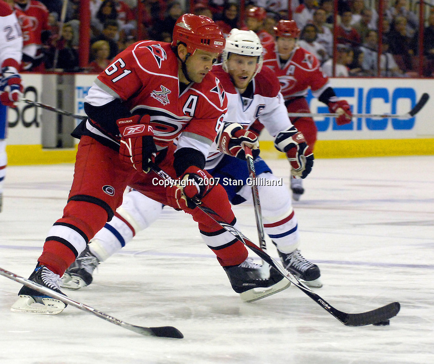 Carolina Hurricanes' Cory Stillman (61) carries the puck defended by the Montreal Canadiens' captain Saku Koivu, in white, during their game Friday, Oct. 26, 2007 in Raleigh, NC. The Canadiens won 7-4.