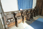 Carved decorated wooden misericord seats in church at Framsden, Suffolk, England, UK