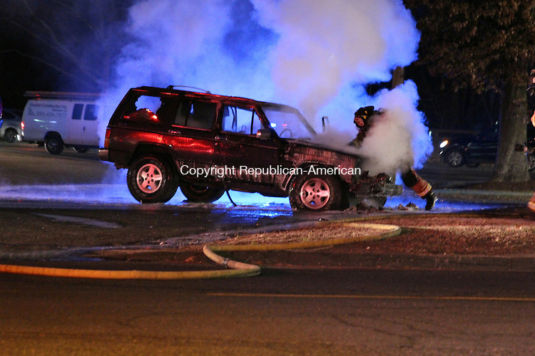 SOUTHBURY, CT: 10 Dec. 2015: 10122015CB04: SOUTHBURY -- After extinguishing a vehicle blaze in Southbury Thursday night, a firefighter opens the hood of a Cherokee Laredo in the Subway parking lot on Oak Tree Road near the intersection of Main Street South. Caleb Bedillion Republican-American