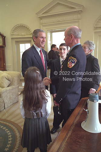 United States President George W. Bush hosts a visit by Bob Beckwith and his family to the Oval Office of the White House in Washington, D.C. on Monday, February 25, 2002.  Mr. Beckwith is the firefighter who stood with the President on top of a crushed fire engine at Ground Zero September 14, 2001..Mandatory Credit: Eric Draper - White House via CNP.