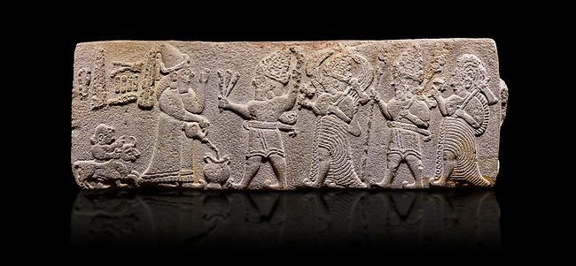Aslantepe Hittite relief sculpted orthostat stone panel. Limestone, Aslantepe, Malatya, 1200-700 B.C. . Anatolian Civilisations Museum, Ankara, Turkey<br /> <br /> Scene of the king's offering drink and sacrifice to the gods. King pours from the pitcher to the vessel (libation); behind the king is a servant bringing a sacrifice. Storm God across the king holds Teshup, a triple lightning bundle - sickle, and a spear-mace set in the other orthostat; the goddess Ishtar holds weapon in both. All six figures have shoes with the curled ends. <br /> <br /> Against a black background.