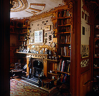 The living room has carved bookshelves and mantelpiece upon which sit Ethiopian Coptic crosses, painted candlesticks and photographs
