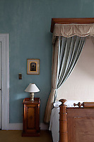 A gilt-edged Victorian painting hangs on the blue-painted wall of a guest bedroom