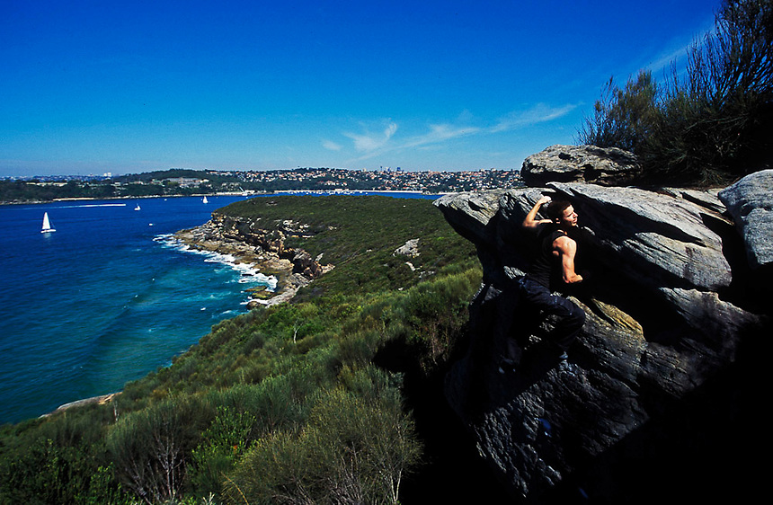 A rockclimber 'tops out' on a boulder problem above Sydney Harbour, Australia, June 2004. Sydney is considered one of the world's best 'climbing cities', with scores of climbing areas in tracts of protected bushland throughout the city. Photo: Ed Giles.