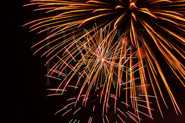 Fireworks orange burst explosion against the night sky in holiday celebration, design elements and backgrounds.