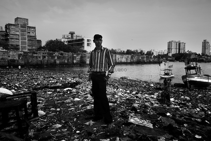 """Mumbai, the city symbolic of the Indian miracle and its sustained economic growth, will become, in 2020, the most populopus metropolis of the world. Today more than 40% of its inhabitants lives in the various slums and shantytowns that define the urban landscape of this Indian """"megacity""""Among the slums, the best known is Dharavi, thanks also to the international success of the Slumdog Millionaire movie..Younge boy posing inside one of the slums in Colaba,May 10, 2007."""